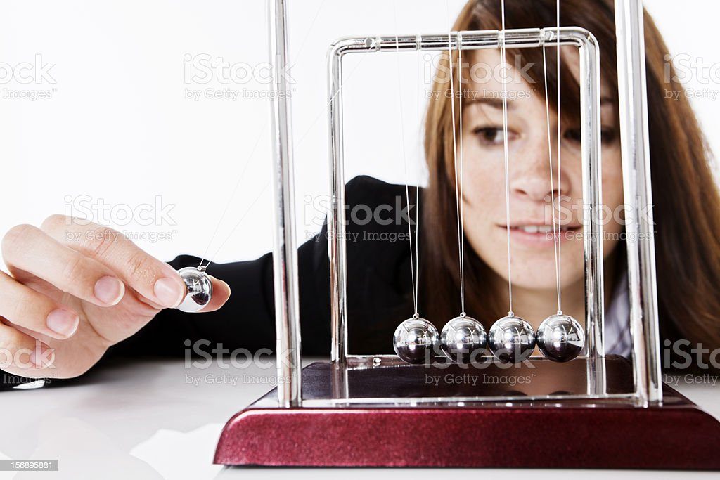Pretty brunette playing with Newtons Cradle executive toy stock photo