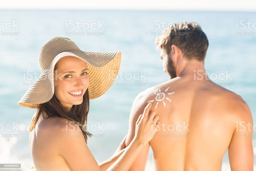 pretty brunette putting sun tan lotion on her boyfriend stock photo