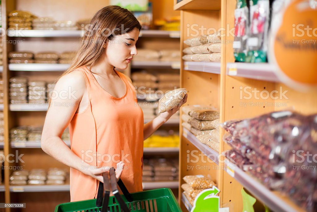 Pretty brunette reading a product label stock photo