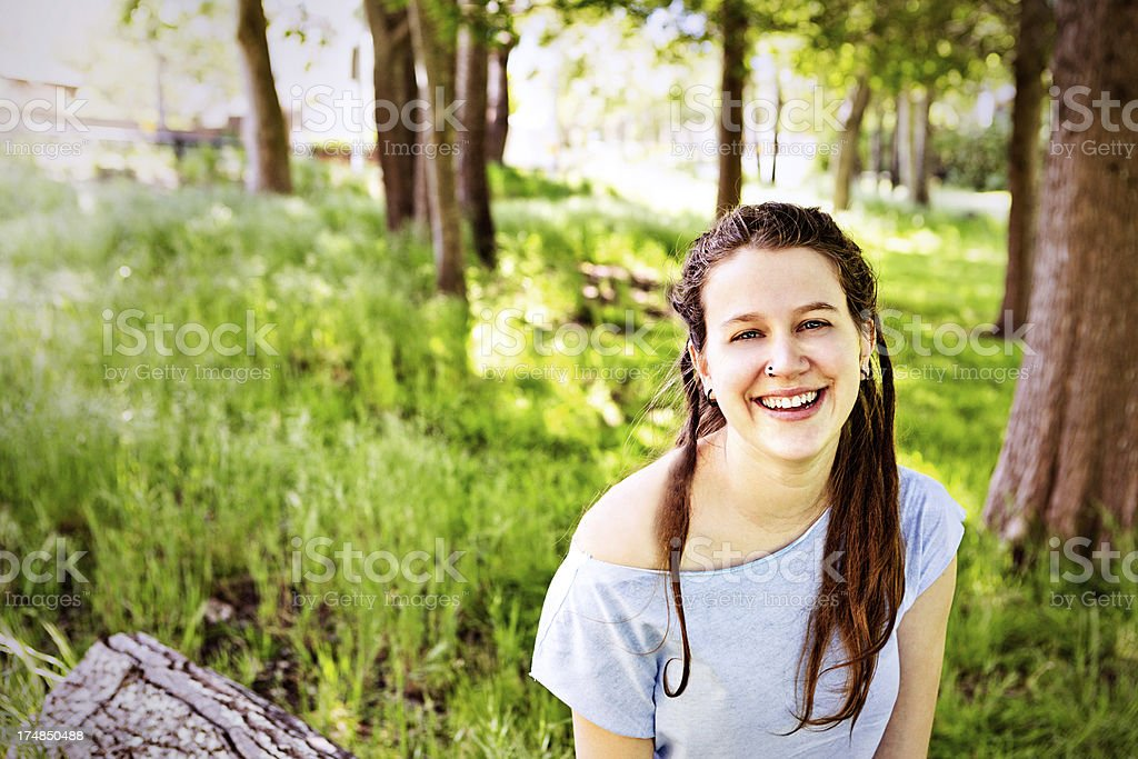 Pretty brunette sitting smiling in forest clearing royalty-free stock photo