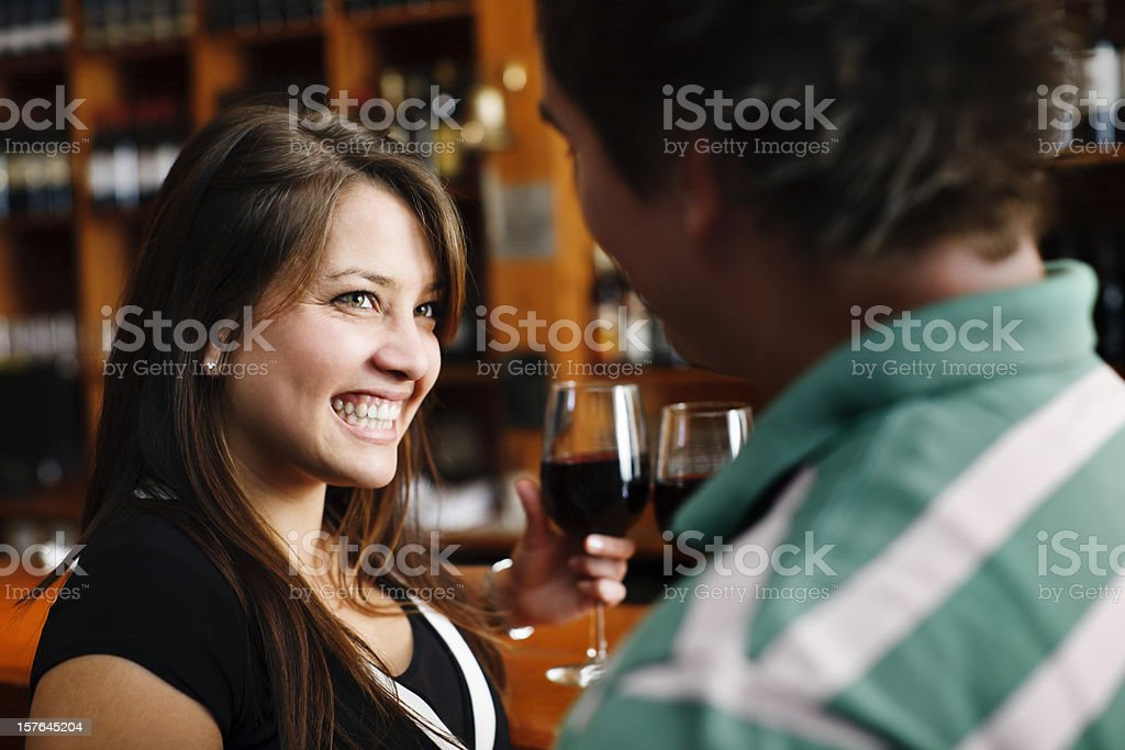 Pretty brunette smiles at man in trendy bar royalty-free stock photo