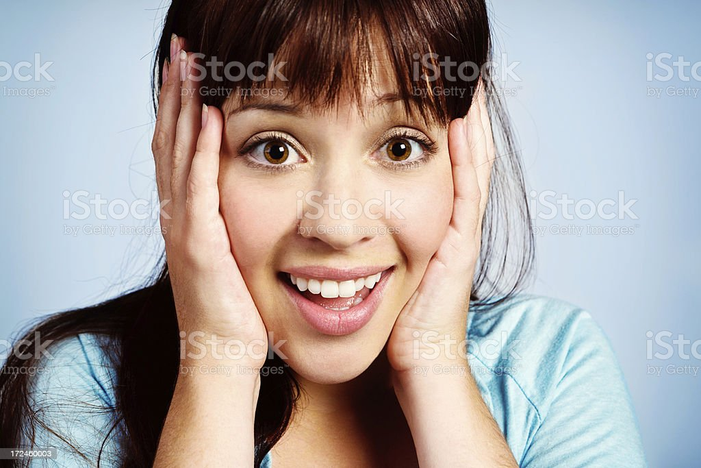 Pretty brunette smiles in delighted surprise, hands to her head royalty-free stock photo