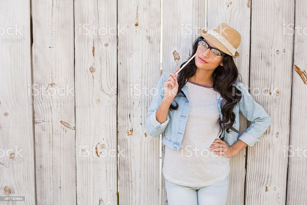 Pretty brunette thinking and smiling stock photo