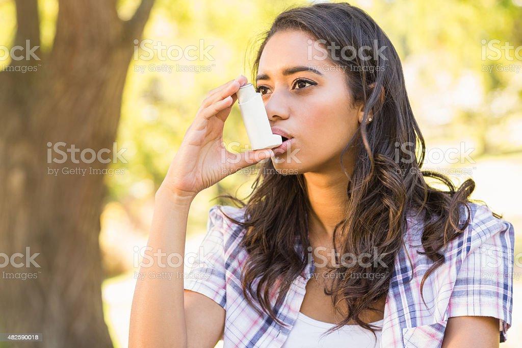 Pretty brunette using inhaler stock photo