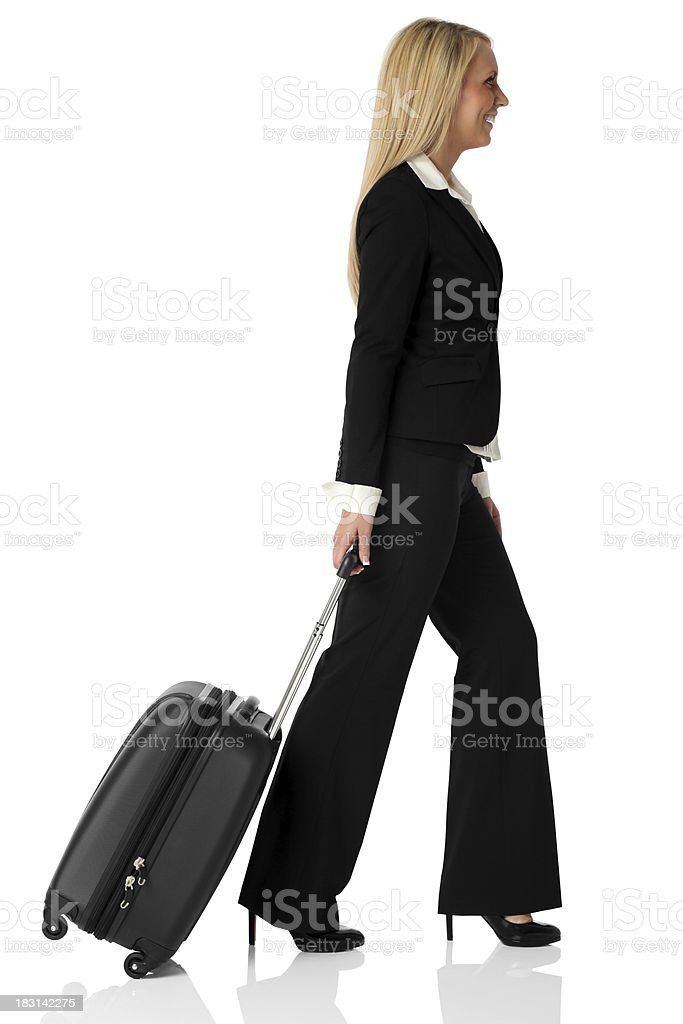 Pretty businesswoman pulling her suitcase royalty-free stock photo