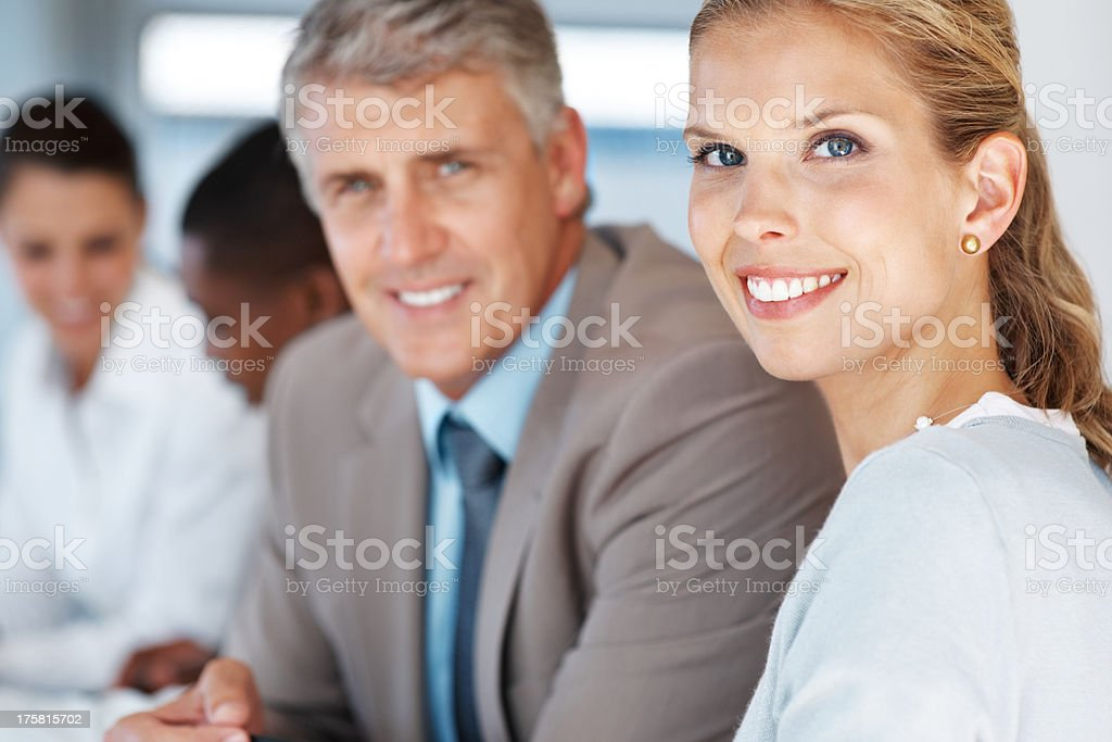 Pretty businesswoman sitting in a meeting with her colleagues stock photo