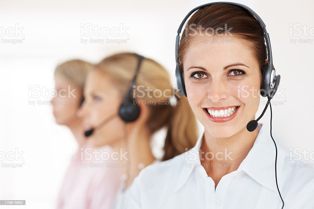 Pretty call center executive with colleagues in background stock photo