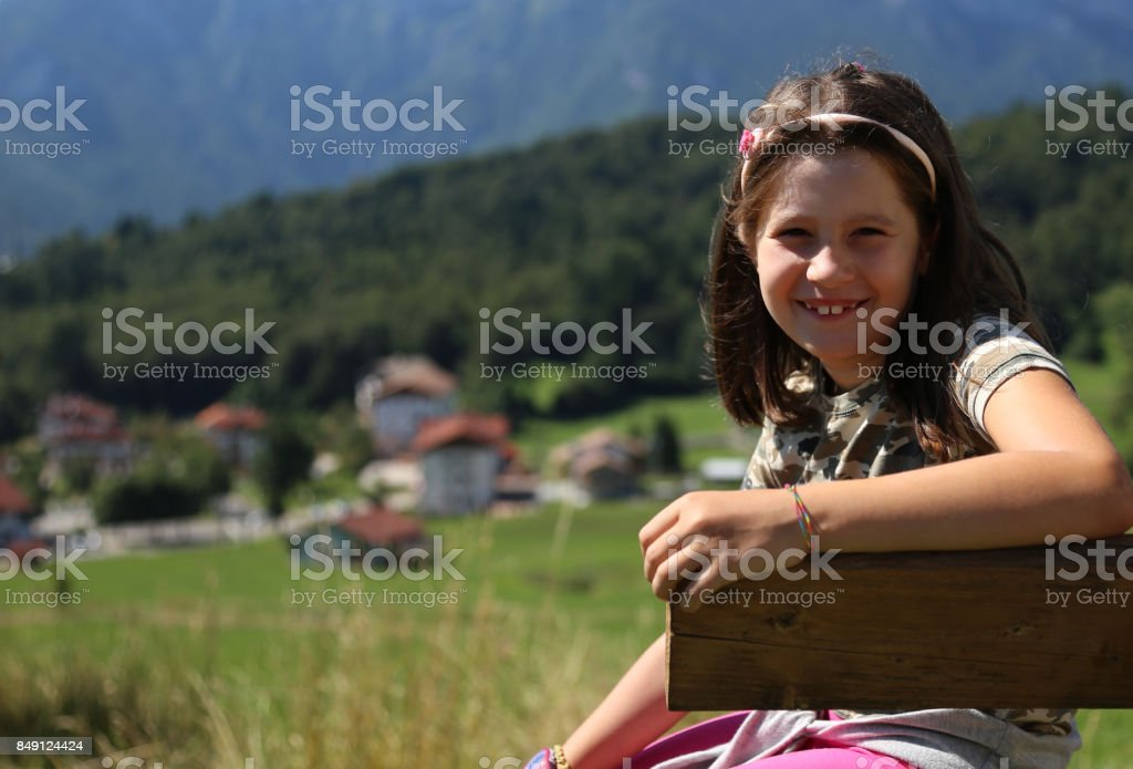 Pretty caucasian little girl with long brown hair smiling on ben stock photo