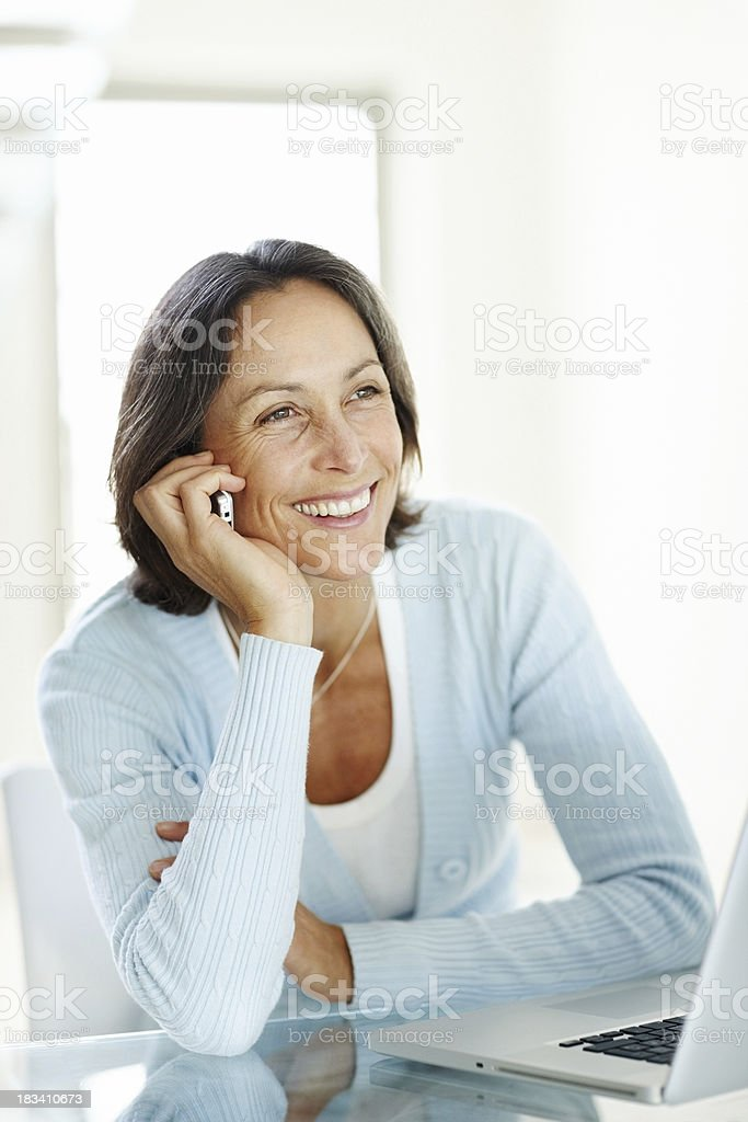 Pretty cheerful mature lady using cellphone with laptop in front royalty-free stock photo