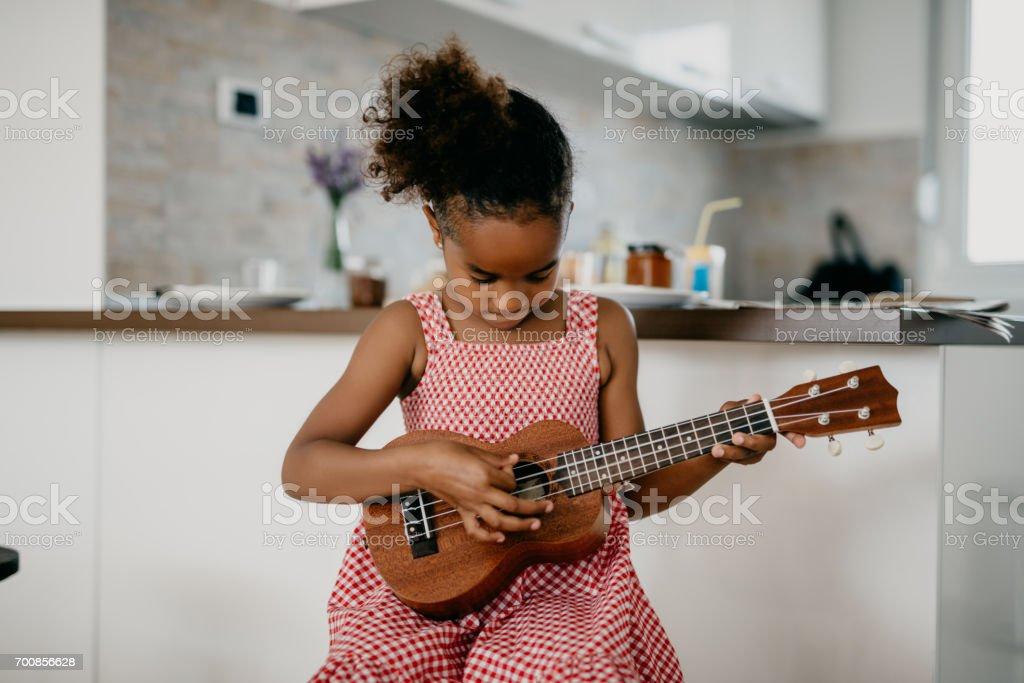 Pretty child with plaid dress plays ukulele stock photo