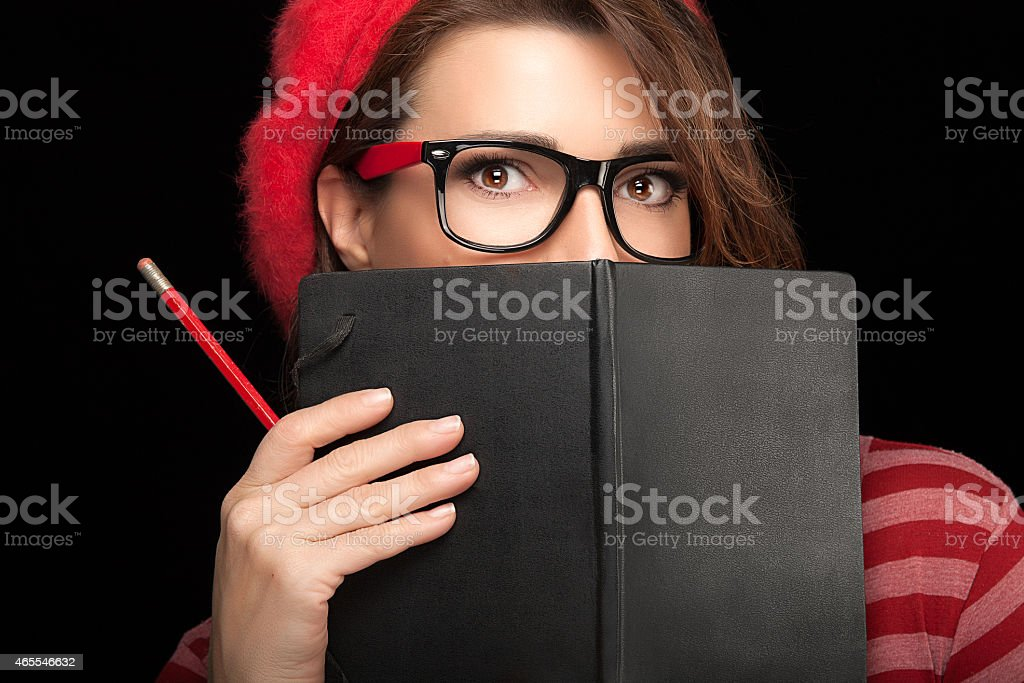 Pretty College Girl Covering her Face with Black Notebook stock photo