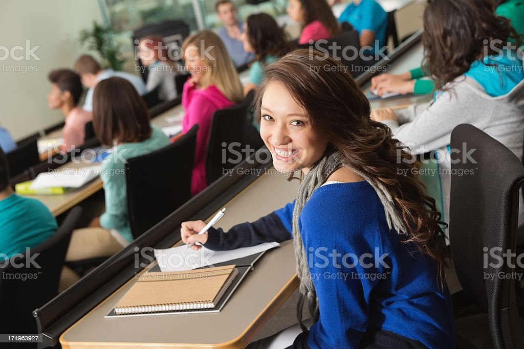 Pretty college student looking back taking study notes during lecture royalty-free stock photo