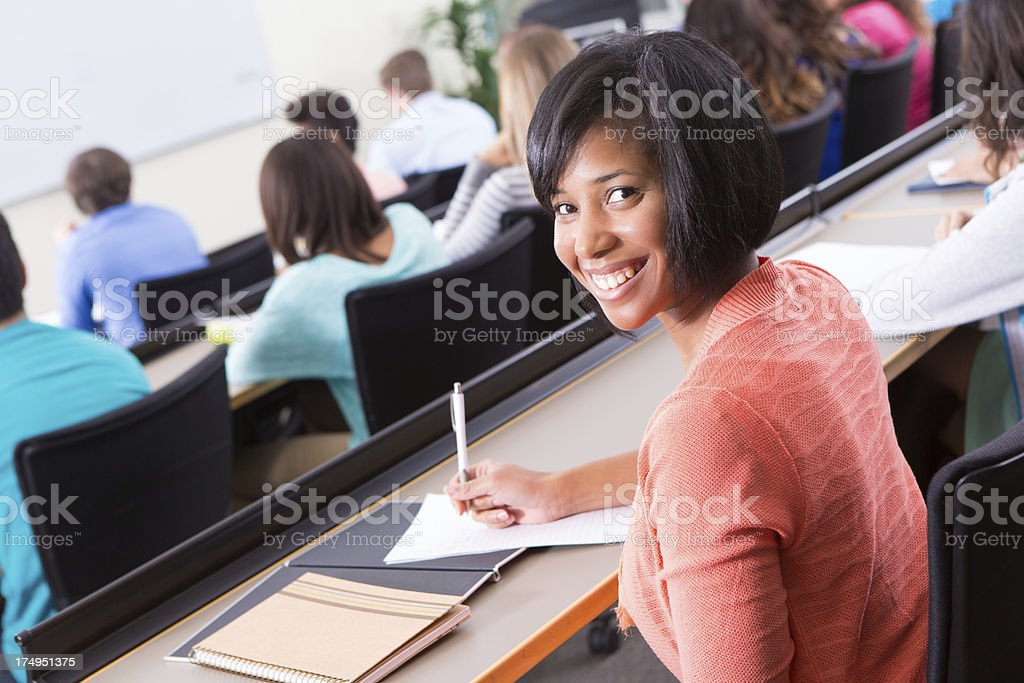 Pretty college student taking notes in lecture hall classroom royalty-free stock photo