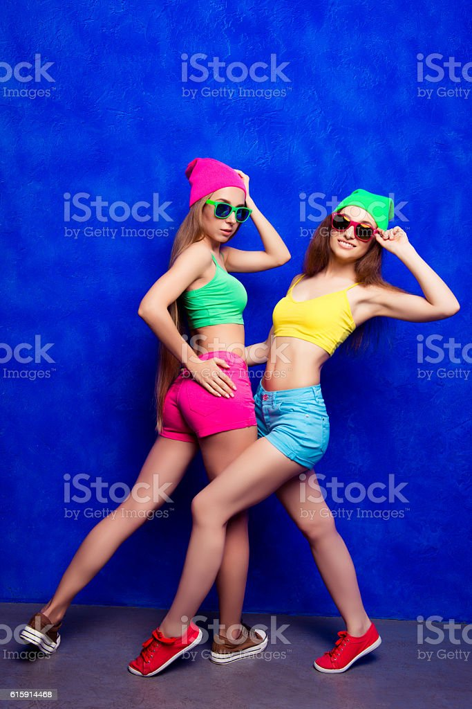 Pretty cool hipster women posing in caps and glasses stock photo