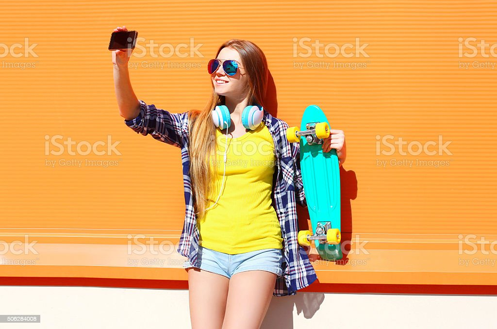 Pretty cool smiling girl in sunglasses with skateboard taking pi stock photo