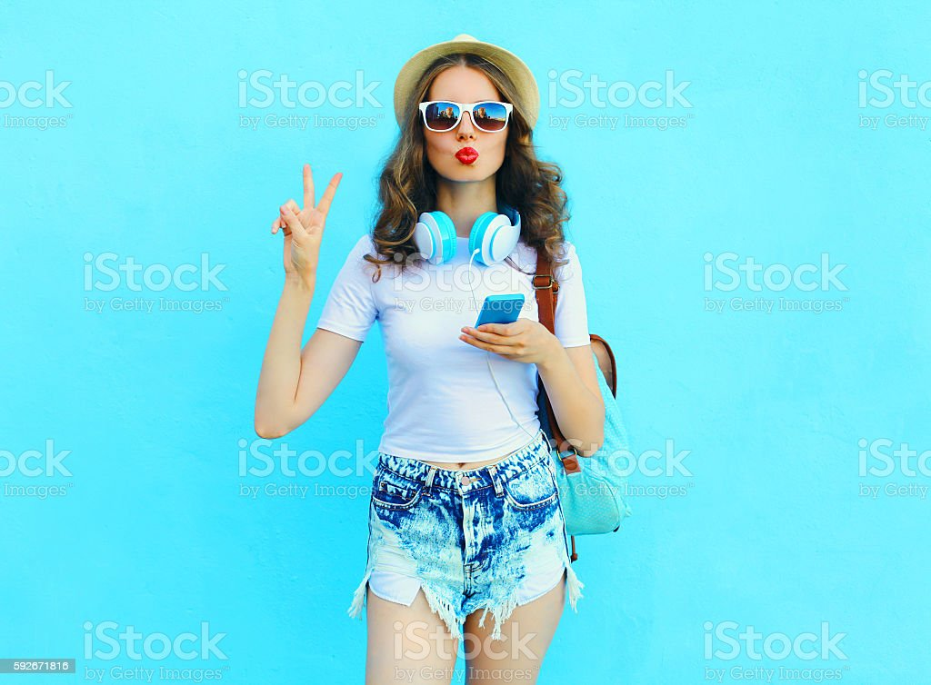 Pretty cool woman listens music and using smartphone over colorf stock photo