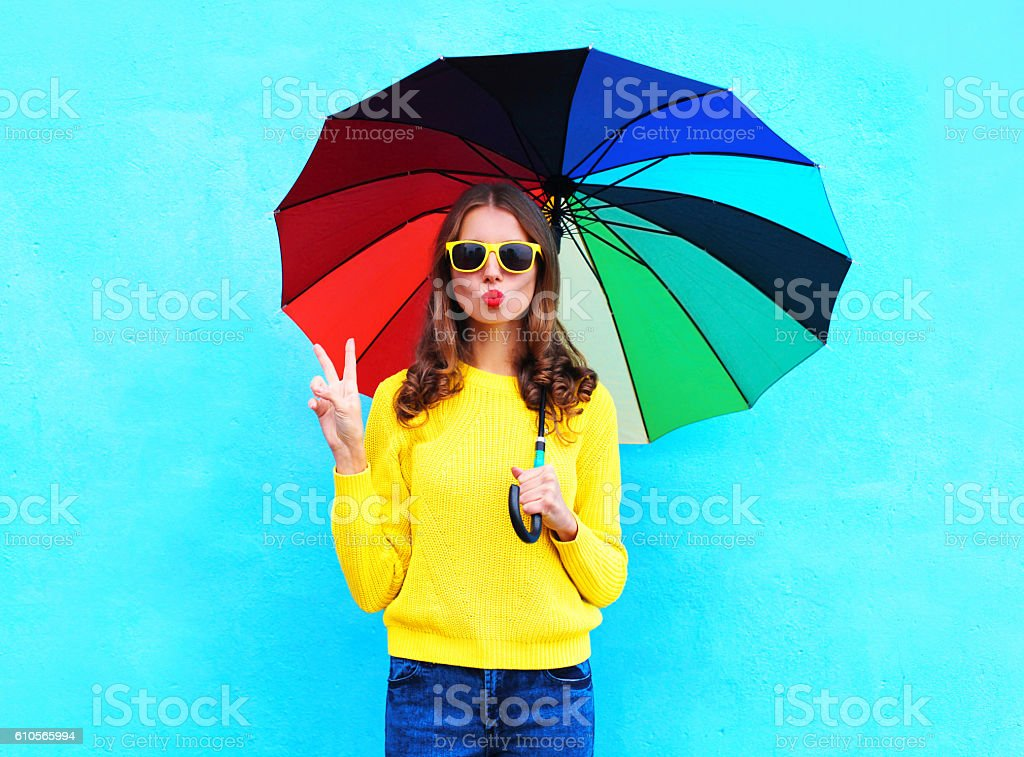 pretty cool woman with colorful umbrella in autumn over blue stock photo