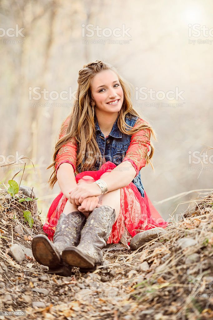Pretty Cowgirl Sitting Alone In The Woods stock photo