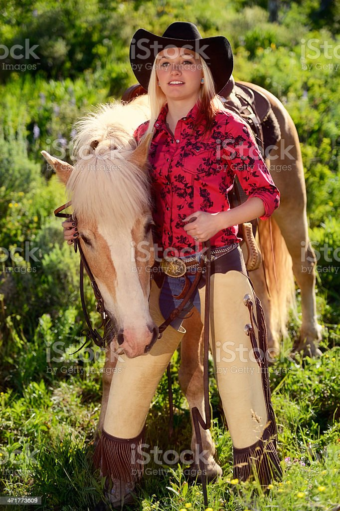 Pretty Cowgirl With Her Palomino Horse Standing In A Meadow royalty-free stock photo