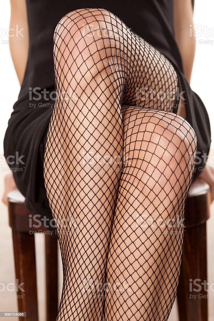 pretty crossed woman's legs in fishnet stockings stock photo