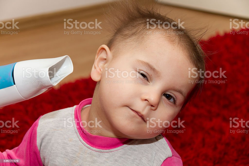 Pretty curly toddler drying her hair stock photo