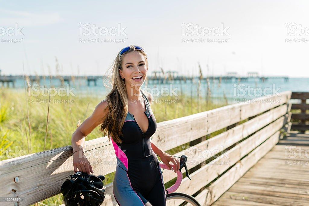 Pretty cyclist resting on boardwalk stock photo
