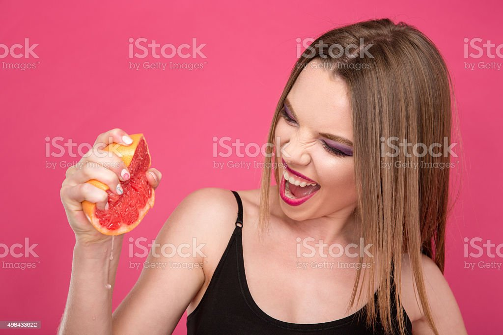 Pretty delighted woman squeezing grapefruit juice by hands stock photo