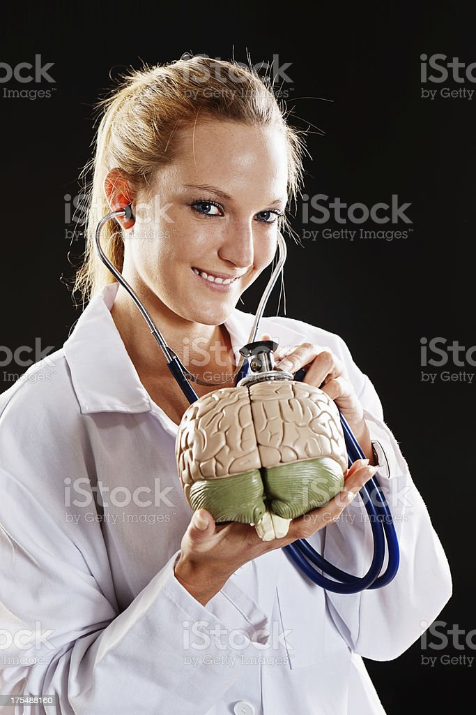Pretty doctor smiles as she uses stethoscope on model brain stock photo