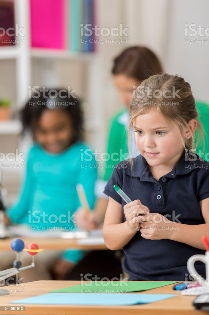Pretty elementary schoolgirl thinks about art project stock photo