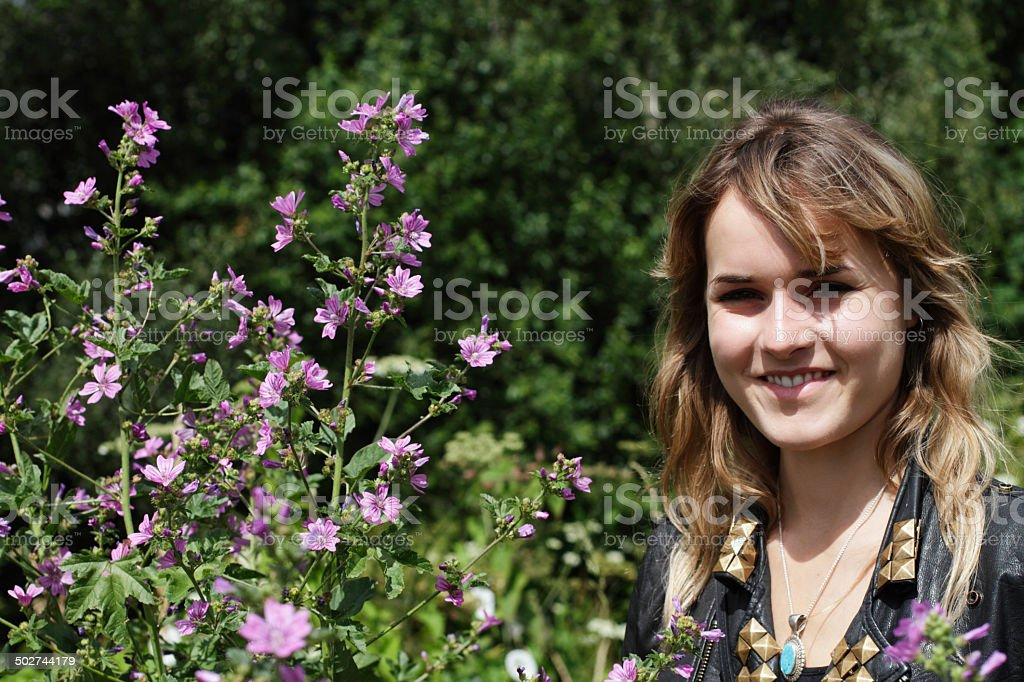 English outdoor girl London with tall tree mallow Malva sylvestris stock photo