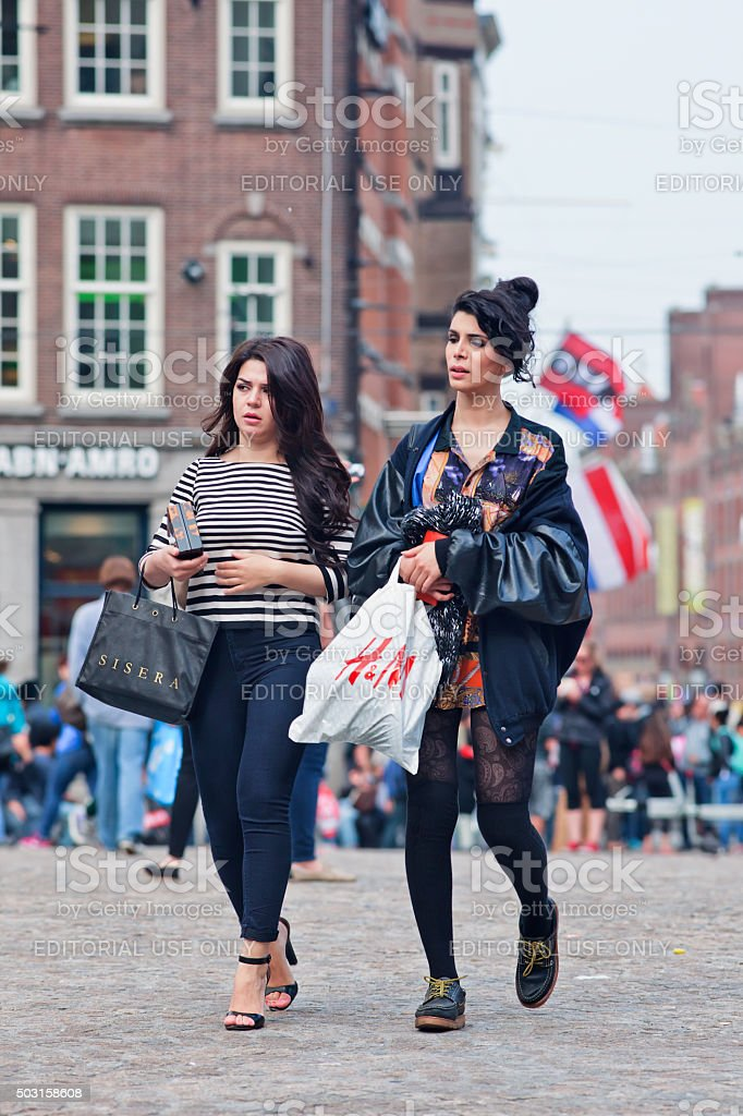 Pretty fashionable women with shopping bags on Amsterdam Dam Square. stock photo