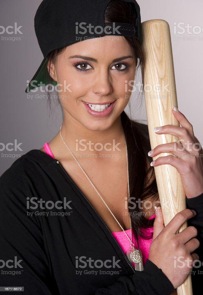Pretty Female Baseball Lover Holds A Wooden Bat and Smiles stock photo