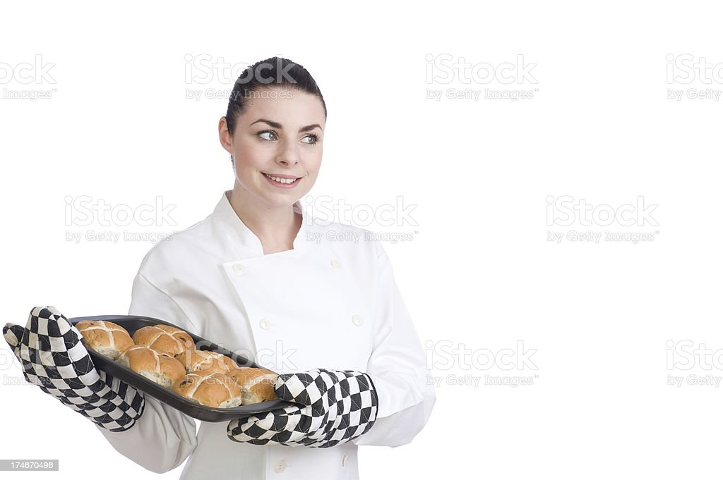Pretty female chef cooks Hot Cross Buns for Easter royalty-free stock photo