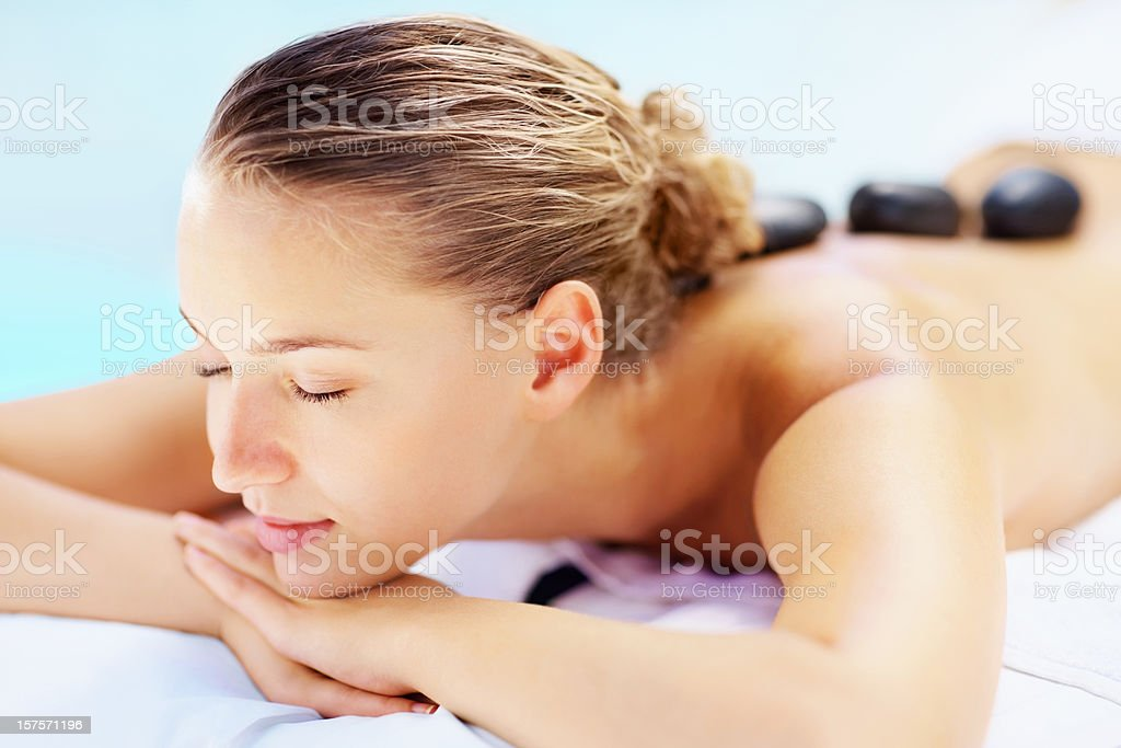 Pretty female enjoying a hot stone therapy at the spa royalty-free stock photo