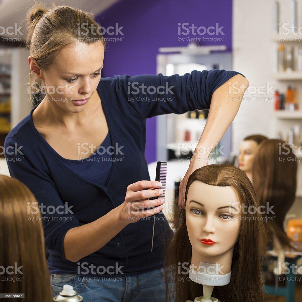 Pretty female hairdresser training on an apprentice head stock photo