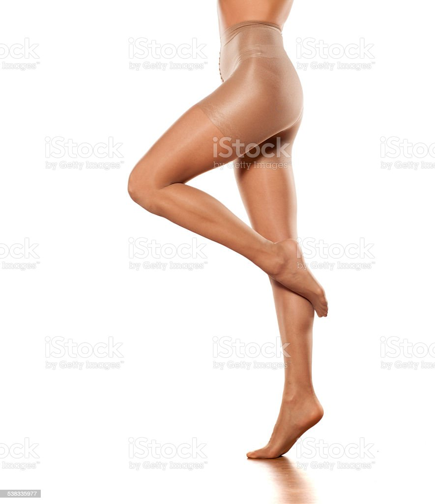 Pretty female legs in stockings on a white background stock photo