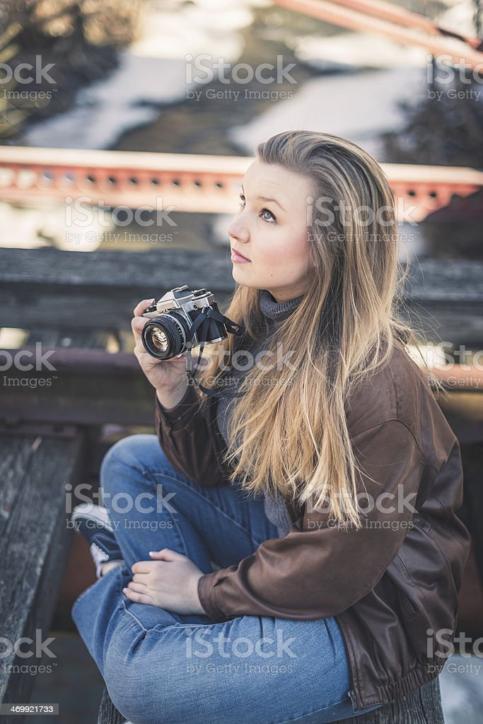 Pretty Female Looking Up Holding an Old Film Camera stock photo