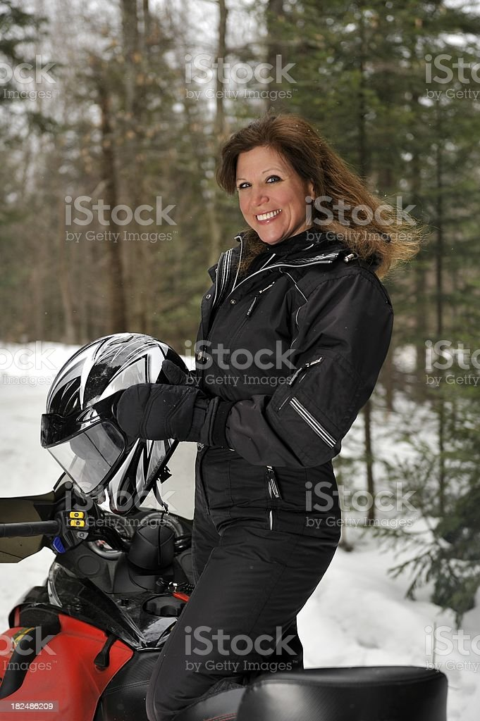 Pretty female snowmobile rider in the snow. stock photo