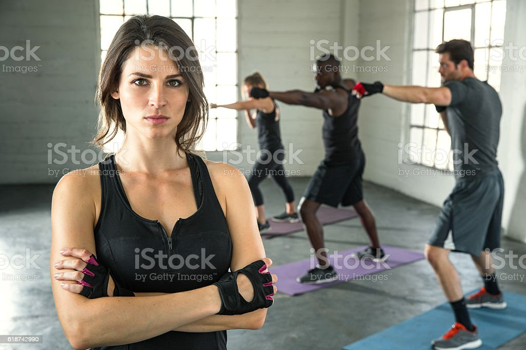 Pretty fit woman pilates instructor glare intensity determination passion leadership stock photo