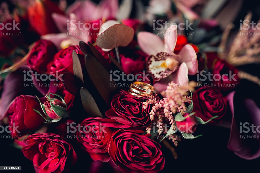 Pretty floral bouquet with wedding rings stock photo