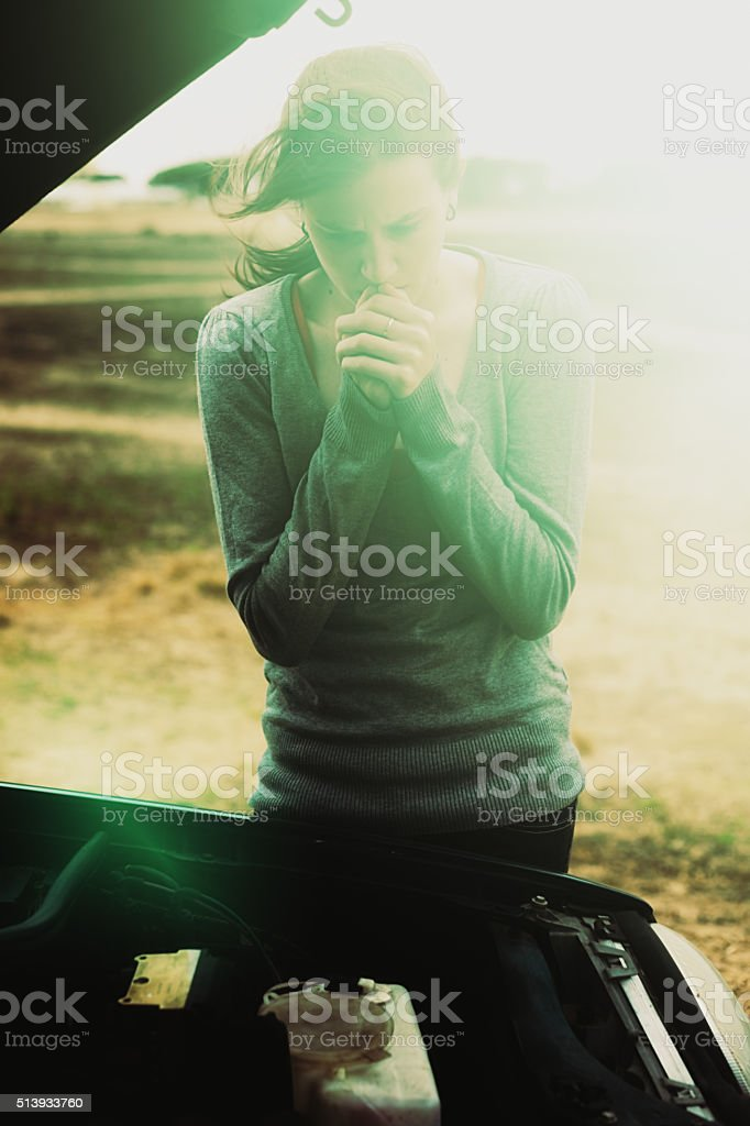 Pretty girl, alone with broken-down car, looks desperate stock photo