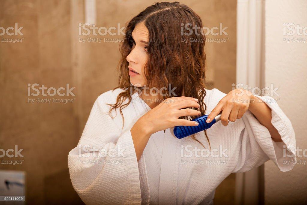 Pretty girl brushing her hair stock photo