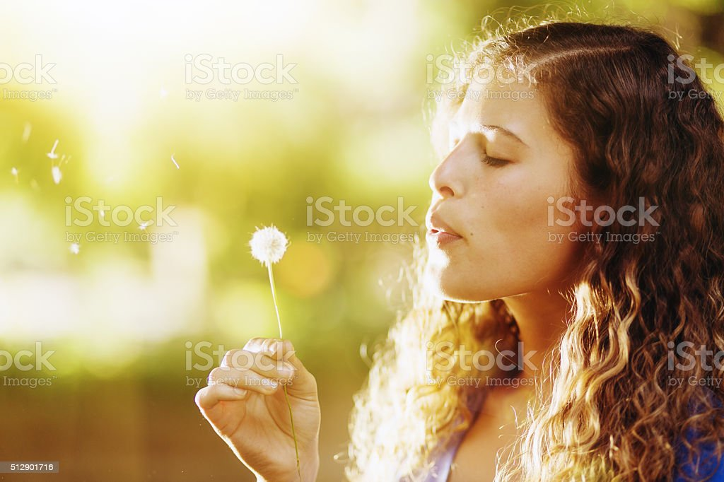 Pretty girl dreamily blowing dandelion seeds  in sunshine stock photo