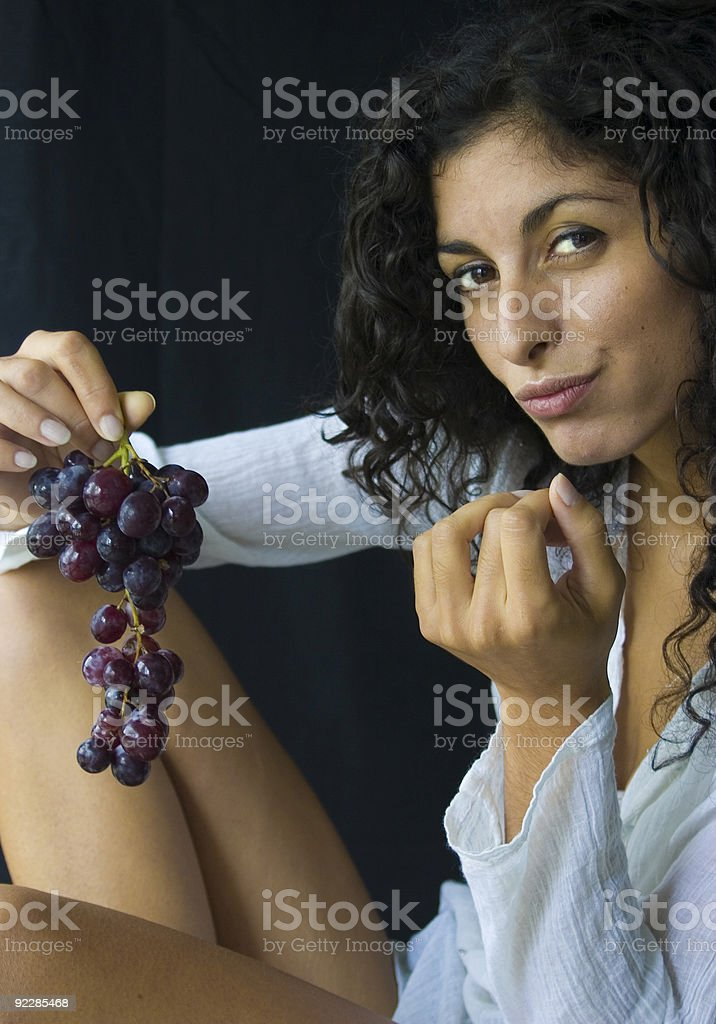 Pretty girl eating grapes. royalty-free stock photo