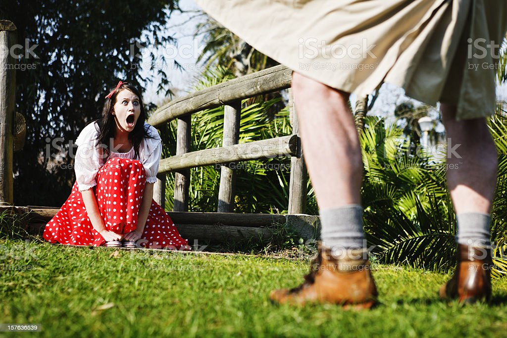 Pretty girl gapes, shocked, as flasher exposes himself in park royalty-free stock photo