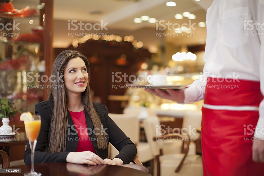 Pretty girl getting a cup of coffee from the waiter royalty-free stock photo