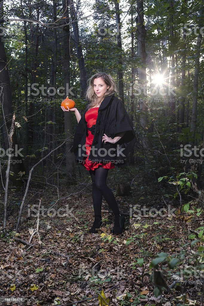 Pretty Girl Holding a Pumpkin in Forest stock photo