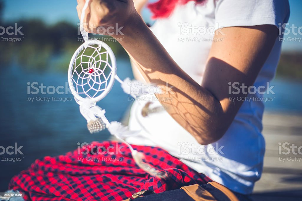 Pretty girl holding dream catcher in her hand stock photo