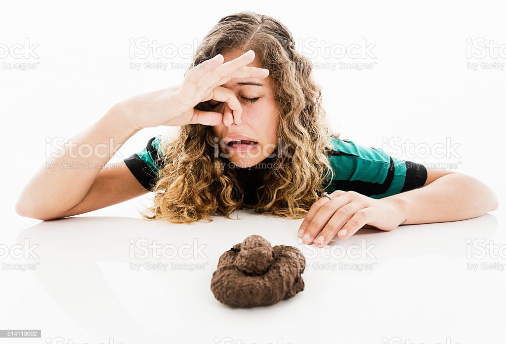 Pretty girl holding her nose and grimacing at dog poo stock photo