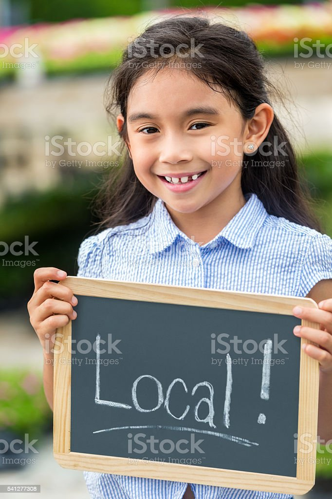 Pretty girl holding local sign stock photo